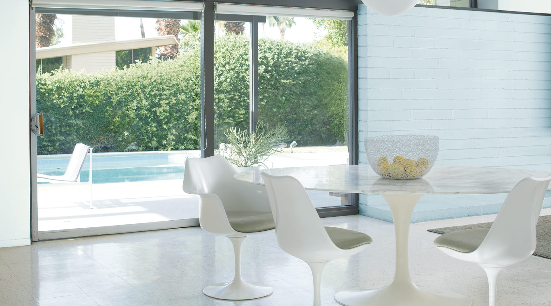 A dining room painted with Benjamin Moore with a view of a pool and greenery outside.