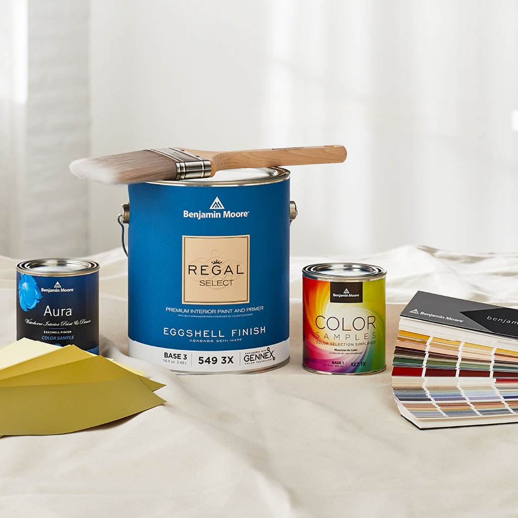 Benjamin Moore paint cans sitting on a painters drop cloth with a paint brush and paint color swatches, a paint project is about to begin.