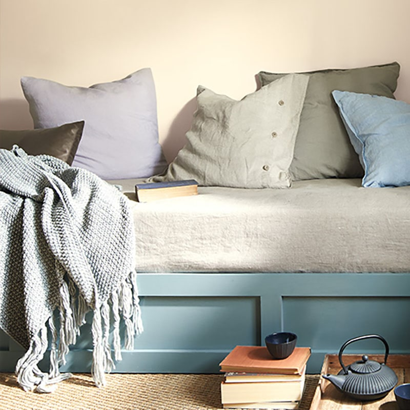 Benjamin Moore Color Trends 2021: Muslin (OC-12), with a daybed scene, blankets, pillows, books, tea and a kettle sitting on the ground