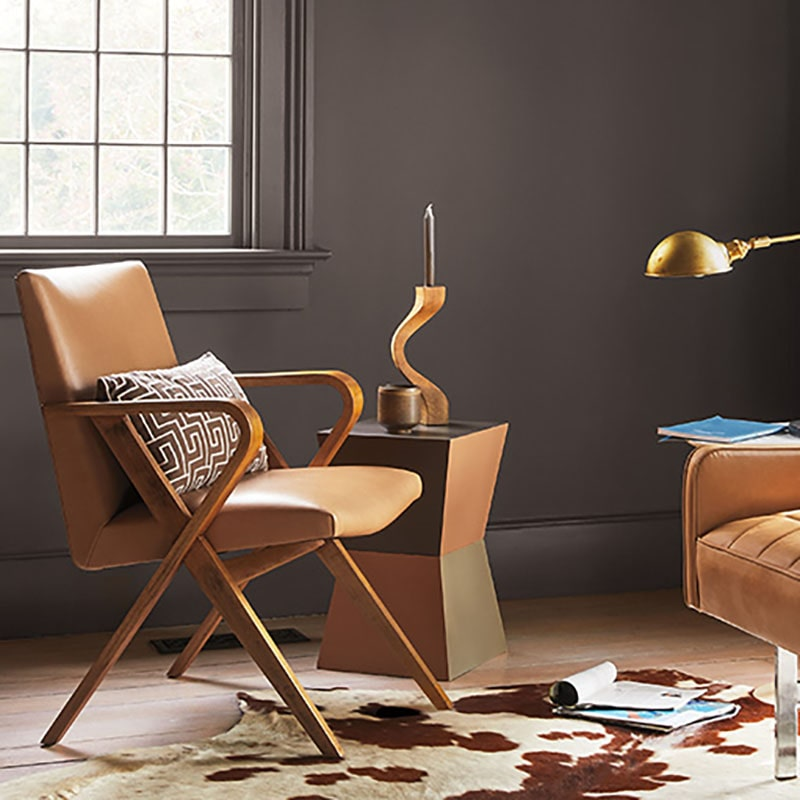 Benjamin Moore Color Trends 2021: Silhouette (AF-655), Living Room Scene with Padded Chair, Side table with candle holder, and a cow print rug