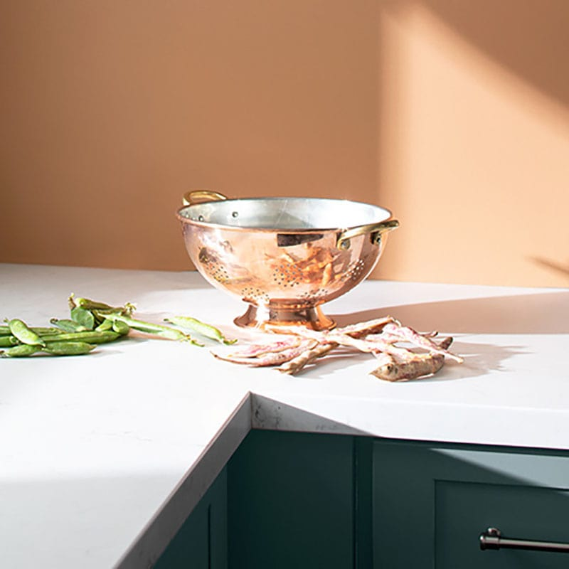 Benjamin Moore Color Trends 2021: Potter's Clay (1221), Kitchen Scene with a rose gold strainer, and string beans on a white countertop