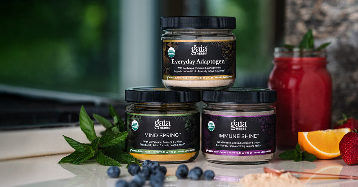 Gaia Herbs products stacked on a counter with fruit