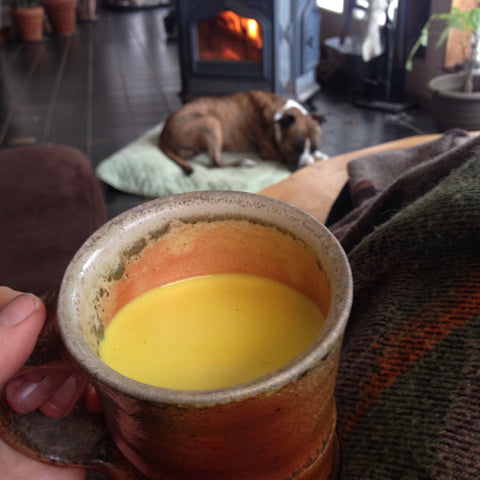 holding golden milk on lap with dog at feet in front of fireplace