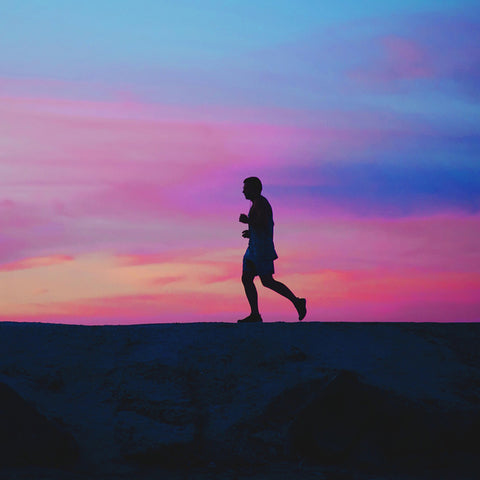Man running with multi colored sunset behind him