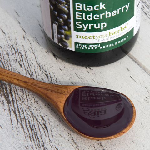Gaia Herbs Black Elderberry Syrup on wooden spoon with bottle in background