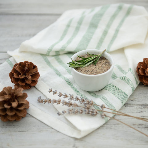 DIY Herbal Exfoliating Face Mask surrounded by herbs and pine cones