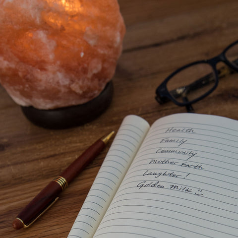 Mindfulness and gratitude journal with salt lamp and glasses on table