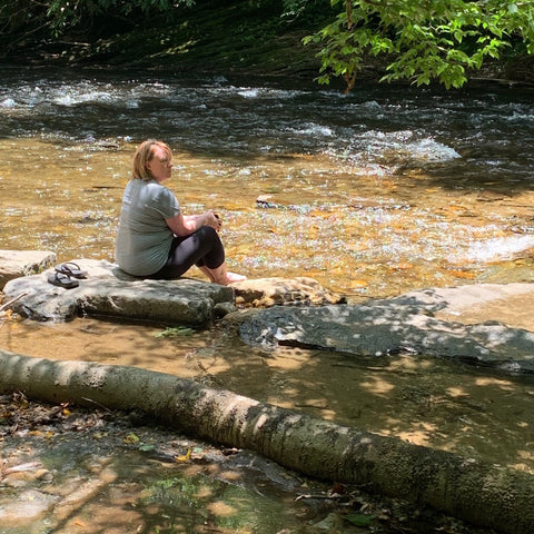 Gaia Herbs employee Kelly ORourke sitting on log in creek