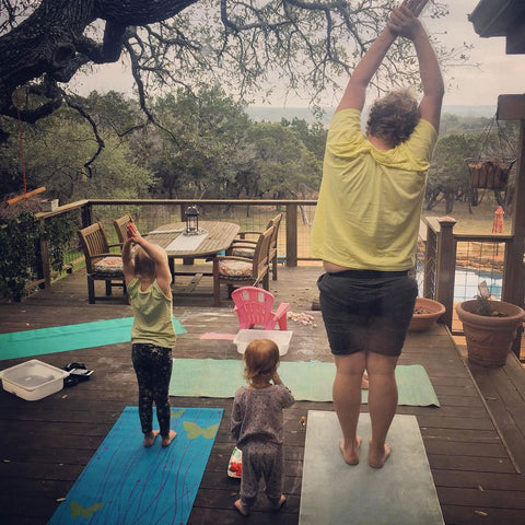 man doing yoga with children on patio