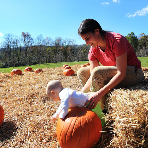Woman and baby playing with pumpkins at Gaia Herbs farm