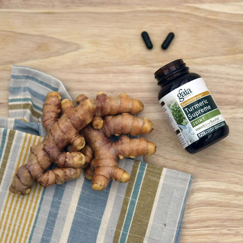 Gaia Herbs Turmeric Supreme Joint surrounded by raw Turmeric