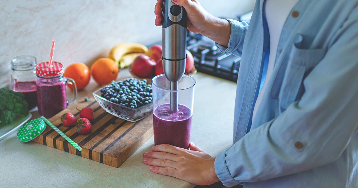 Woman blending smoothie with fresh fruit
