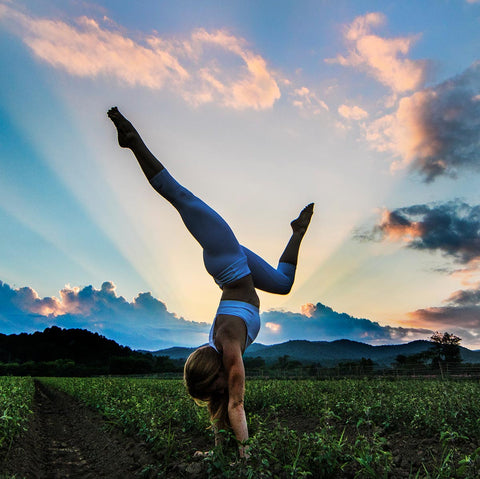 woman doing yoga at gaia herbs farm during sunset