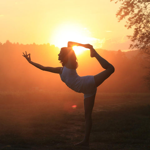 woman doing sunset yoga at gaia herbs farm