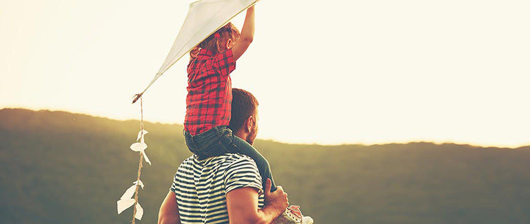 Child on father's shoulders flying kite