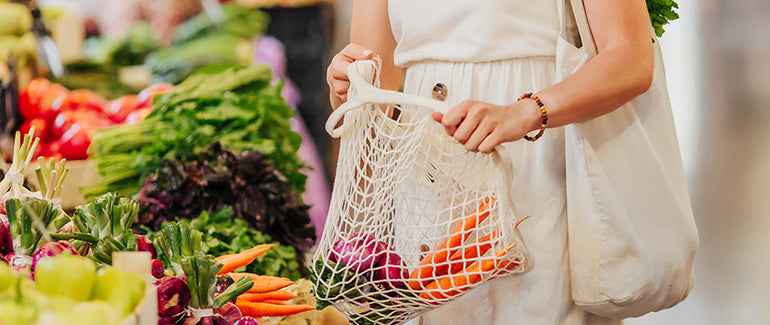 woman shopping fresh produce with reusable bag