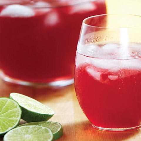 Elderberry punch on table with limes on the side