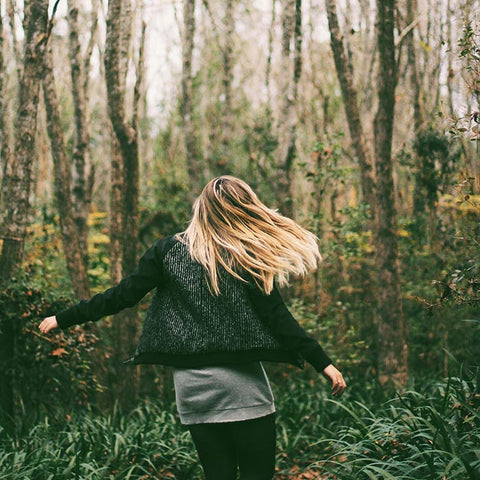 blonde haired woman twirling in woods