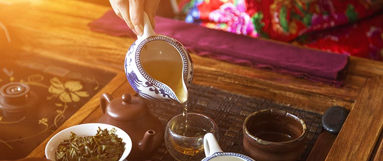 woman pouring green tea into mug