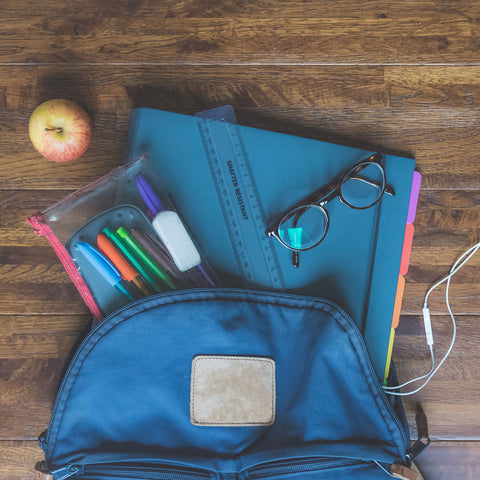 backpack full of pens and folders with an apple and glasses on the side