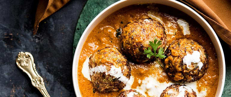 Malai Kofta in white bowl on granite table with gold spoon on left
