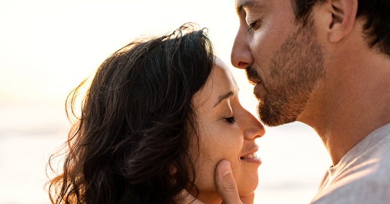 Man getting ready to kiss a woman with bright beach background