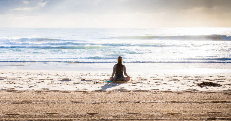 Woman practicing self care by meditating at the beach