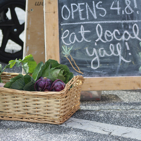 local farmers market sign with basket of veggies in front