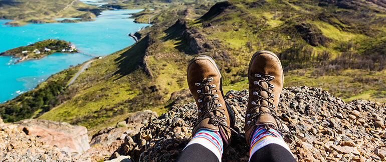 hiking boots of woman sitting on top of mountain