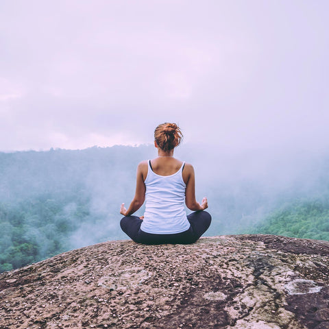 woman meditating on cliff ledge