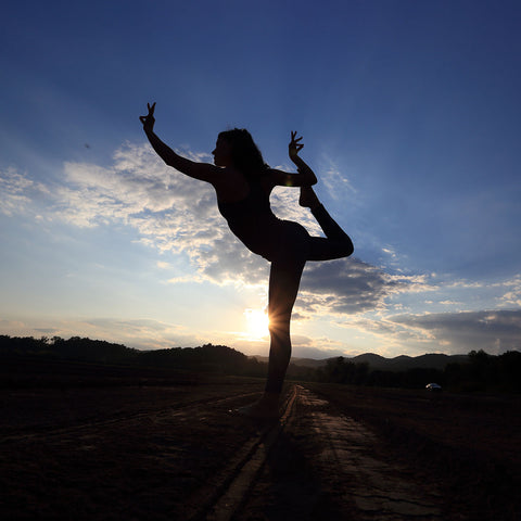 silhouette of woman doing yoga in field at Gaia Herbs farm