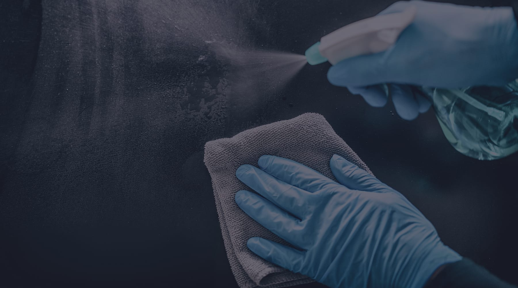 A person spraying a disinfectant cleaner wearing nitrile gloves and holding a cloth. Shop disinfectants and cleaners online at JC Licht in Chicago, IL.