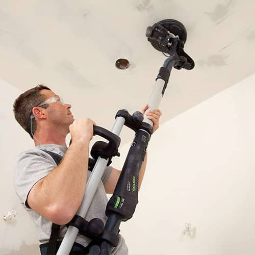 A man using a Festool drywall sander, available at JC Licht in Chicago, IL.