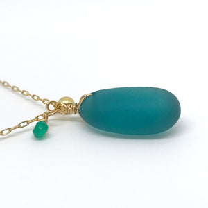 teal seaglass necklace with solid 14k gold charm and green garnet stone on gold chain kriket broadhurst side view