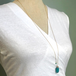 teal seaglass necklace with solid 14k gold charm and green garnet stone on gold chain kriket broadhurst shown on model