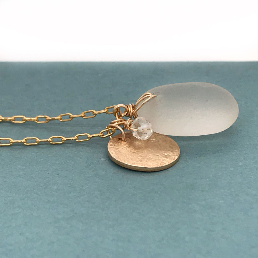 gold necklace with clear seaglass pendant and gold disc charm kriket broadhurst jewellery