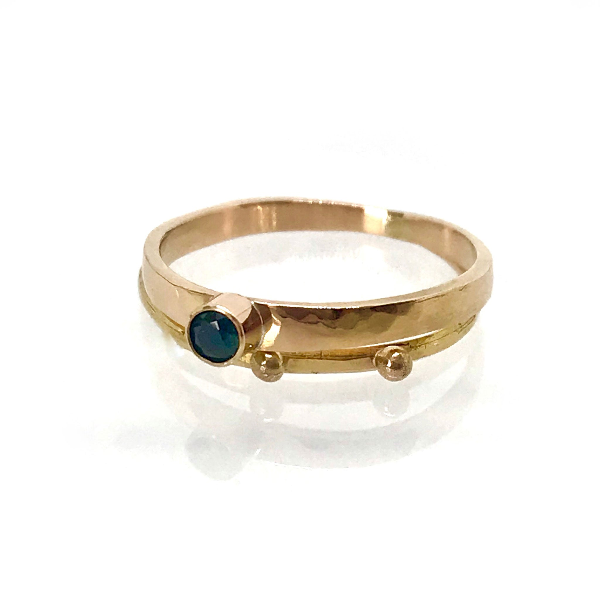 pair of gold rings with blue green parti sapphire bezel set in 14k gold Kriket Broadhurst jewellery
