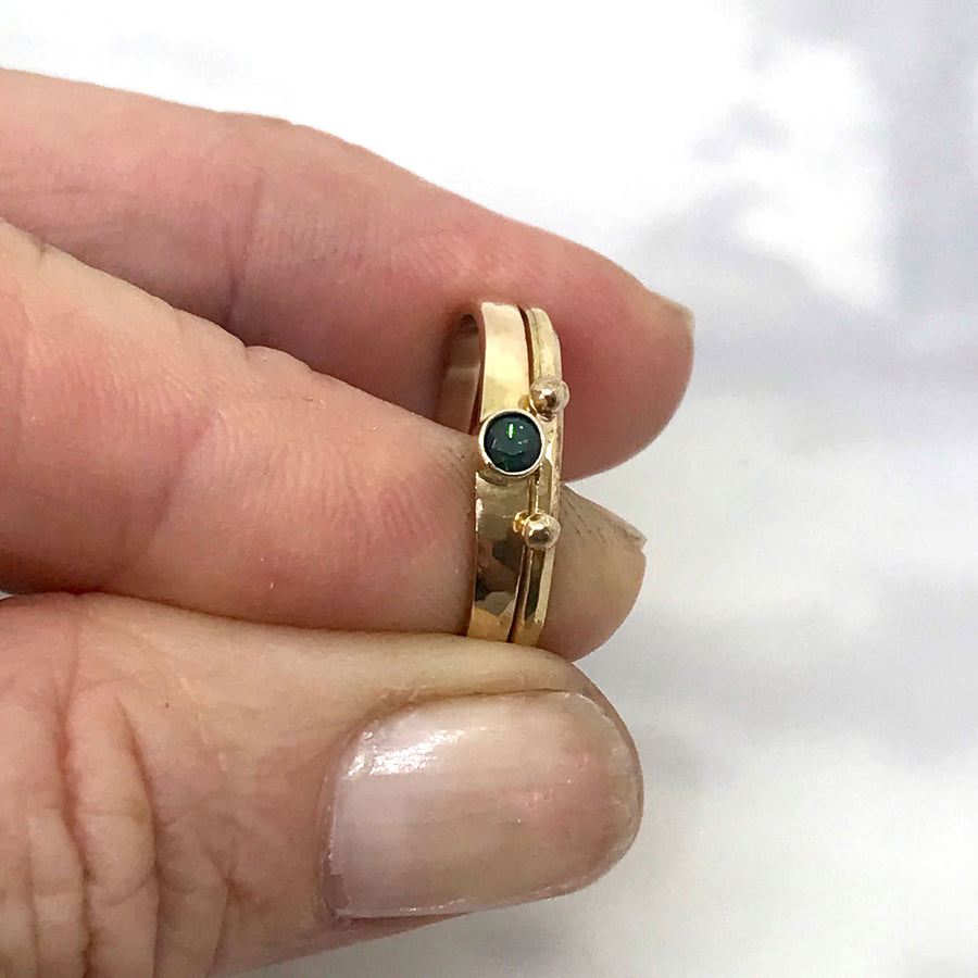 pair of gold rings with blue green parti sapphire bezel set in 18k gold Kriket Broadhurst jewellery