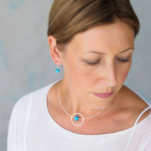Kriket broadhurst jewellery Sterling silver necklace featuring a beautiful floating hammered silver circle and a turquoise handmade ceramic bead on a sterling silver cable wire shown on model with matching earrings.