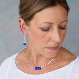 Cornflour blue ceramic blue earrings on sterling silver shown on model with matching necklace Kriket Broadhurst jewellery