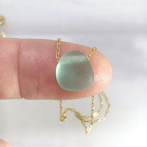 Aqua seaglass necklace on gold chain with aquamarine stone on fingertips kriket broadhurst jewellery