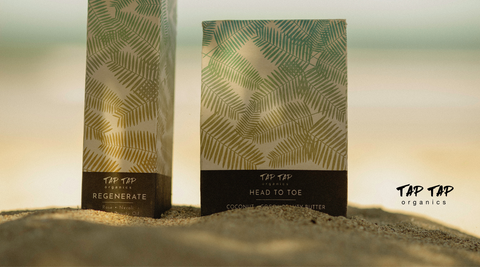 Tap Tap Organics Regenerate Beauty Oil box and Head To Toe Beauty Butter box on the sand