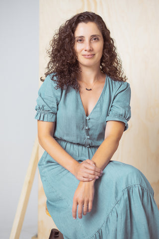 Portrait of Patricia Fonseca, founder of Tap Tap Organics. She is sitting on a stool, with a blue dress and small smile.