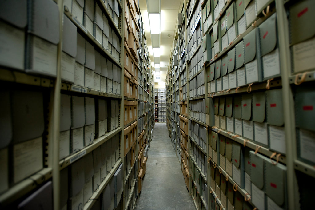 Photograph looks down a long aisle of metal shelving filled to the brim with archival boxes.