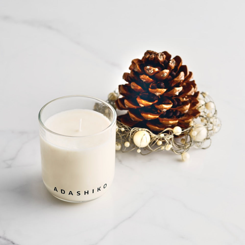 Adashiko Candle - sitting on a shelf next to pine cone Christmas decoration | Adashiko Collagen | 100% Natural Skin Care