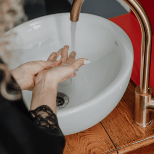 woman in black lace robe washing her hands at round sink with copper gooseneck tap