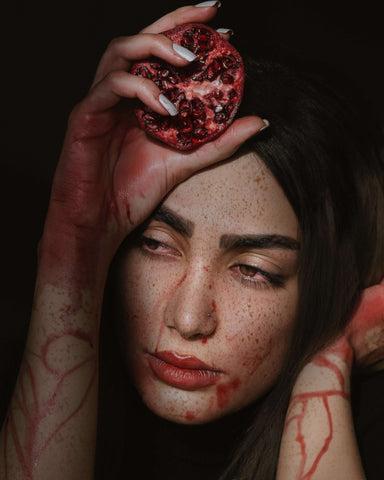 woman with dripping pomegranate  occult vibe