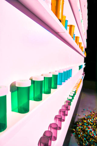 colorful plastic bottles on pink lit shelf