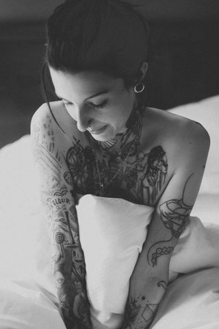 tattooed woman in white sheets