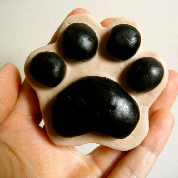 Hand holding a paw shaped soap vegan